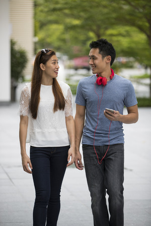 Happy Asian couple walking down the street. Young Asian man and woman walking together.