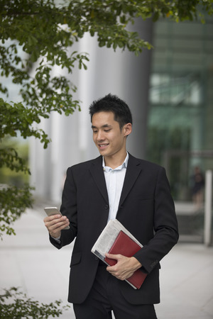 well read: Asian business man talking reading his smart phone.