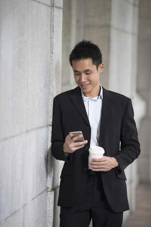 homme d'affaires asiatique talking lisant son téléphone intelligent.