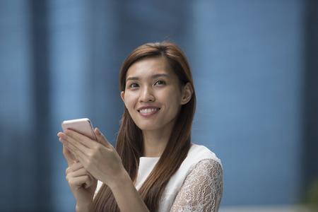 femme d'affaires asiatique en utilisant son téléphone intelligent à l'extérieur.