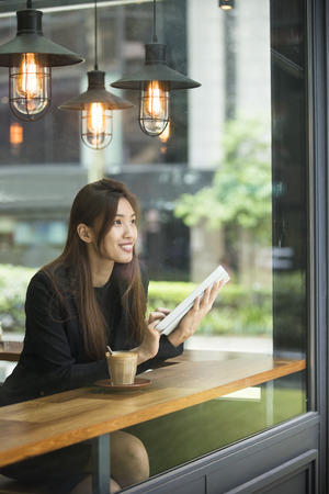 Businesswoman asiatique avec une tasse de café tout en lisant son ordinateur tablette dans un café.