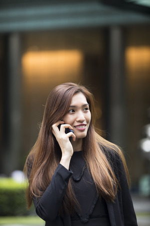 Asian business woman using her smart phone outside.