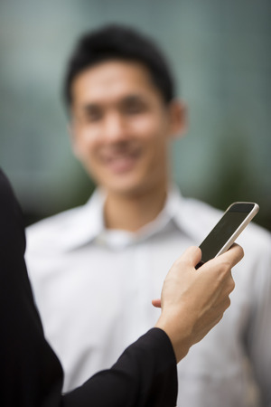 Close up of businesswomans hand using a smart phone. Businessman blurred in background.