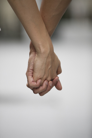 Close up of a man and woman holding hands together