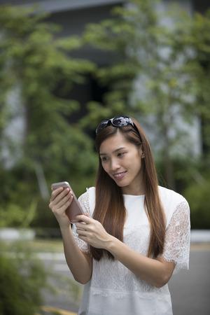 Portrait de la belle jeune femme asiatique en utilisant son téléphone portable dans la rue.