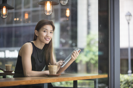 millennial: Asian Businesswoman with a cup of coffee while reading her tablet computer in a cafe.
