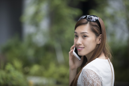 Portrait of beautiful young Asian woman using her mobile phone in the street. Banque d'images