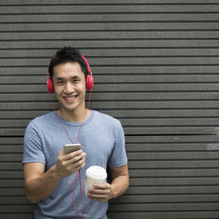 Happy Asian man casual dressed with headphones and smart phone. Leaning on grey wall.
