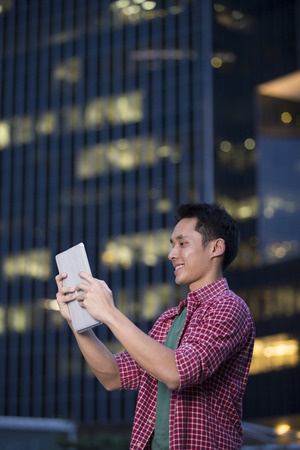 Chinese man using his digital tablet PC in city at night.