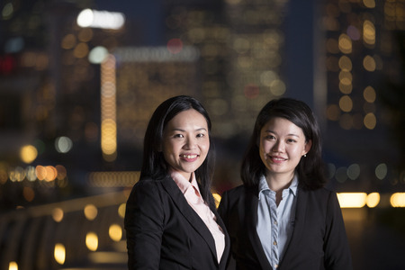 Portrait of two Asian Businesswomen Looking directly at the camera in city at night.
