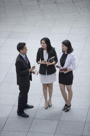 Vue en plongée de trois hommes d'affaires asiatiques parler dehors. Banque d'images