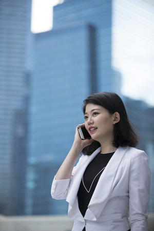 Asian businesswoman talking on smart phone outside the office. Banque d'images