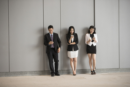 Group of Asian business colleagues using there mobile phone's. Standing next to a wall.