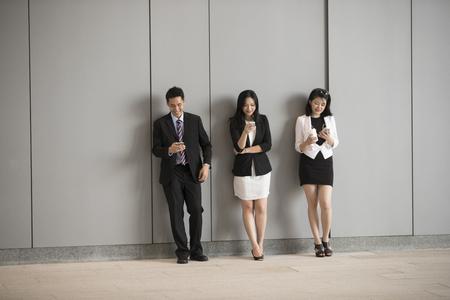 Groupe de collègues d'affaires asiatiques utilisant des téléphones mobiles. Debout à côté d'un mur.