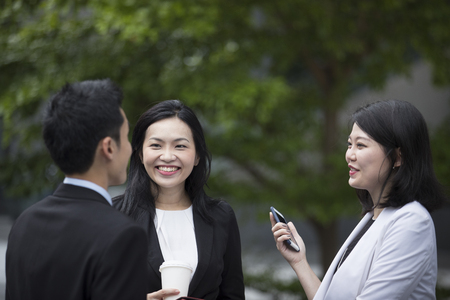 Three Asian Business women and man talking outside.