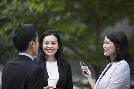 Trois femmes d'affaires asiatiques et homme parlant extérieur.