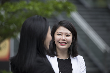 Deux femmes d'affaires asiatiques parlent bureau à l'extérieur.