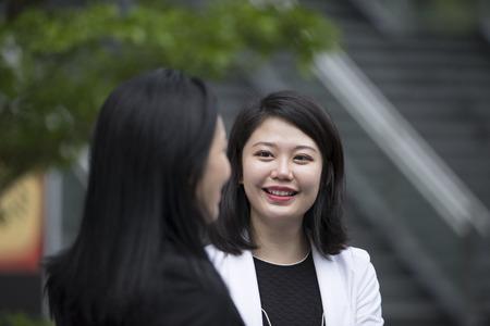 Two Asian Business women talking outside office.