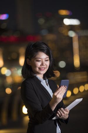 Femme d'affaires chinoise debout à l'extérieur en utilisant son téléphone intelligent dans la ville la nuit.