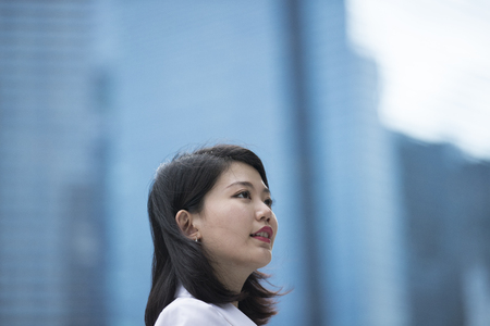 Portrait of a young asian business woman standing outside.