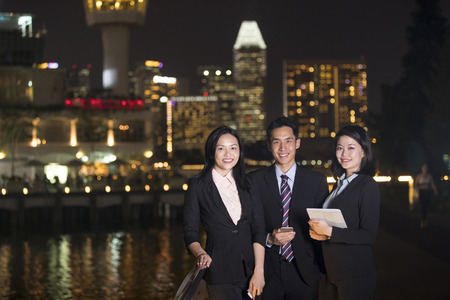Happy Chinese Business colleagues in city at night. Stock Photo