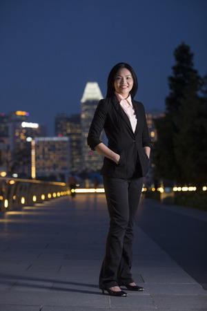 Asian businesswoman in smart business suit in city at night.