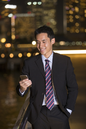 chinese businessman: Chinese businessman using his smart phone in city at night.