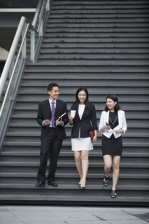 Three Asian  Business people talking while walking down stairs outside. Stock Photo