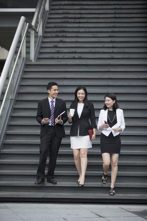 down the stairs: Tres personas de negocios hablando mientras camina por las escaleras fuera.