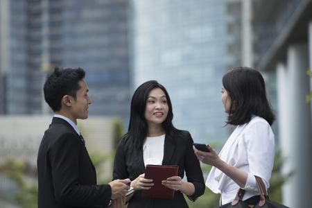 men talking: Three Asian Business women and man talking outside.