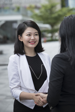 Two asian business woman shaking hands outside the office.