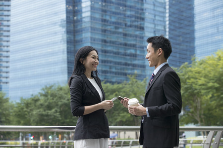 Two Asian Business colleagues talking outside in modern Asian city. Banque d'images