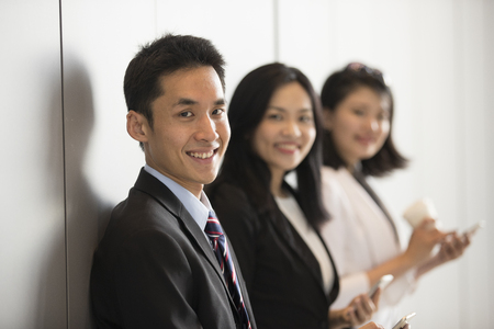 Portrait of three Asian business people standing in a row.