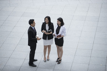Elevated view of three Asian Business people talking outside.