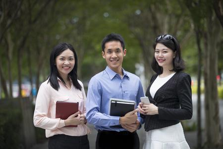 Portrait de trois hommes d'affaires asiatiques debout dans une rangée.