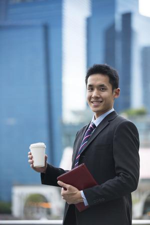 Portrait d'un homme d'affaires asiatique debout à l'extérieur en ville.
