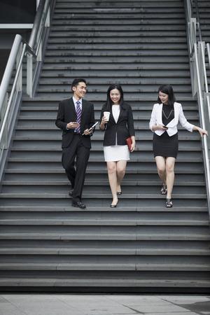 bajando escaleras: Tres personas de negocios hablando mientras camina por las escaleras fuera.