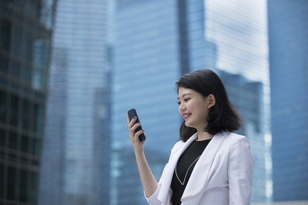 happy work: Asian businesswoman talking on smart phone outside the office. Stock Photo