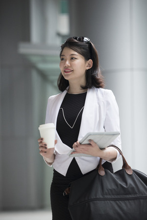 asian businesswoman: Portrait of a young asian business woman standing outside.