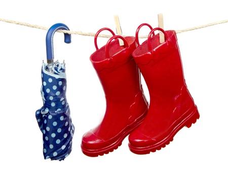 rain boots: Botas rojas de lluvia y un paraguas azul cuelgan a secar en un tendedero de ropa. Aislado en un fondo blanco