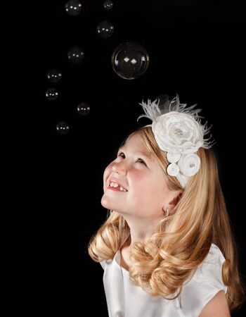 A cute girl wearing a white dress and white headband looking up at bubbles. With a black background