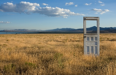 An antique or vintage door standing alone in a grassy feild, with mountains and a bueatiful sky in the background. Stock Photo