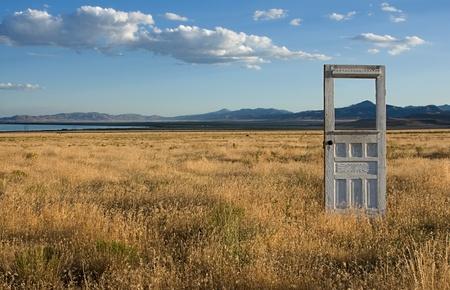 porte ancienne: Une porte antique ou vintage debout seul dans un feild herbeuse, avec des montagnes et un ciel bueatiful dans le fond. Banque d'images