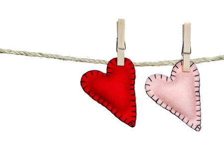 Two stiched valentine hearts pink and red on a clothes line. They are handmade out of felt. Isolated on a white background