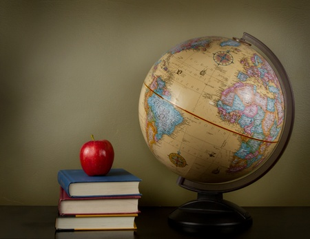An apple sitting on top of three books, sitting next to a globe of the world. A blank area in background for text. photo