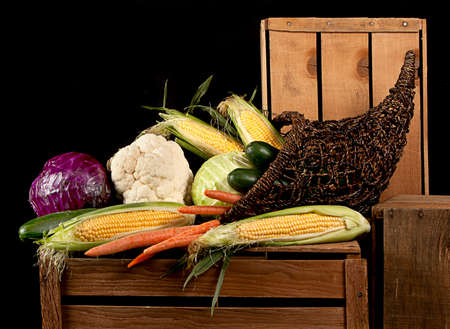 A cornucopia of vegtables all starting with the letter c, including corn, carrots, cucumbers, cabbage, cauliflower, sitting on wooden crates. Against a black background. photo