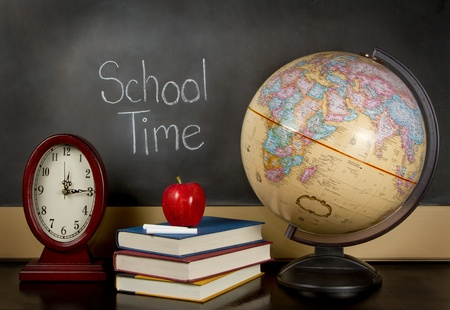 school time: a chalkboard with the words school time written on it, a clock, books, apple, chalk and a globe sit on a teachers desk.