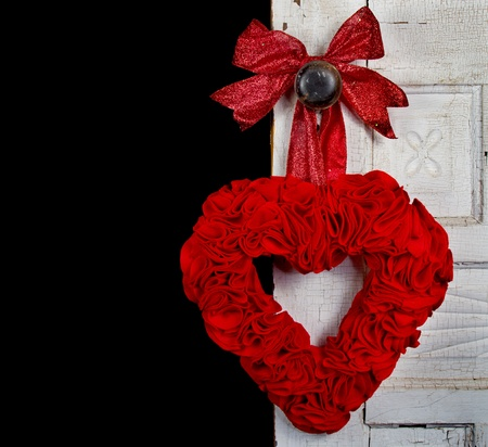 a handmade felt heart with a bow hanging on the door knob of a vintage or antique door, against a black background photo
