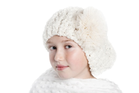 an attractive girl in a white winter hat and wearing a white shawl, she has blue eyes and is isolated on a white background. Stock Photo - 12157505