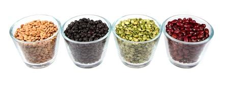 leguminosas: Cuatro tipos de legumbres en los recipientes de vidrio, lentejas, frijoles negros, guisantes majados, y frijoles rojos. Aislado en un fondo blanco Foto de archivo